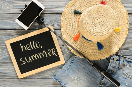 Womens clothing, accessories (denim shorts, straw hat, cellphone, selfie stick, chalkdoard) on grey wooden background. Text Hello summer. Trendy fashion outfit. Shopping, travel concept.  Flat lay. Summer concept Standard-Bild - 98798014