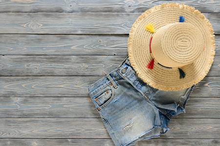 Womens clothing, accessories (denim shorts, straw hat) on grey wooden background with copy space. Trendy fashion outfit. Shopping concept. Mock up for online store.  Flat lay. Summer collection Standard-Bild - 98840791