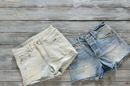 Womens clothing (denim shorts) on grey wooden background with copy space. Trendy fashion outfit. Shopping concept. Mock up for online store.  Flat lay. Summer collection Standard-Bild - 98779752