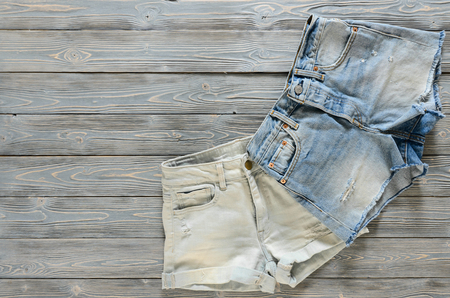 Womens clothing (denim shorts) on grey wooden background with copy space. Trendy fashion outfit. Shopping concept. Mock up for online store.  Flat lay. Summer collection Standard-Bild - 98820031