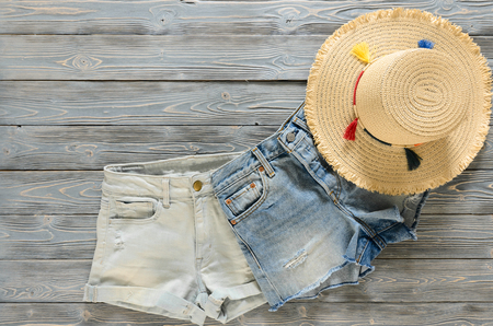 Womens clothing, accessories (two denim shorts, straw hat) on grey wooden background with copy space. Trendy fashion outfit. Shopping concept. Mock up for online store.  Flat lay. Summer collection Standard-Bild - 98806132