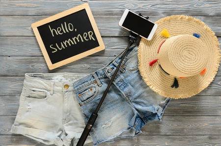 Womens clothing, accessories (denim shorts, straw hat, cellphone, selfie stick, chalkdoard) on grey wooden background. Text Hello summer. Trendy fashion outfit. Shopping, travel concept.  Flat lay. Summer outfit Standard-Bild - 98798089