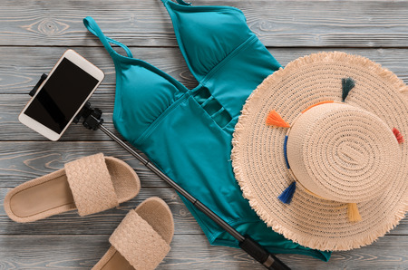 Womens clothing, accessories, shoes (straw hat, blue green swimsuit, flip flops, cellphone, selfie stick) on grey wooden background. Trendy fashion outfit. Shopping, travel, summer, beach, vacation concept, abstract.  Flat lay Standard-Bild - 98798090