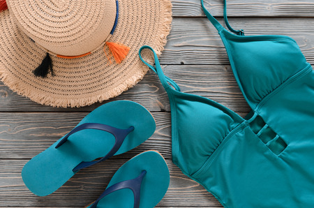 Womens clothing, accessories, shoes (straw hat, blue green swimsuit, flip flops) on grey wooden background. Trendy fashion outfit. Shopping, travel, summer, beach concept, abstract.  Flat lay Standard-Bild - 98895330