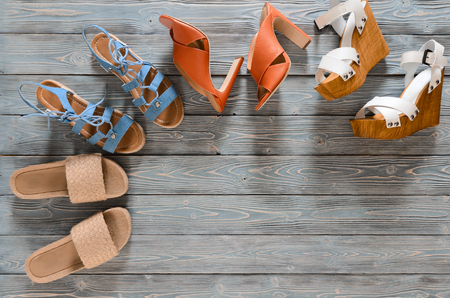 Set of womens shoes (wedges, heels and flat sandals) on grey wooden background. Spring summer collection. Flat lay. Fashion concept. Template for online store, coupon, offer, promotion, discounts, gift card, deals Standard-Bild - 98917389