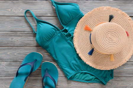 Womens clothing, accessories, shoes (straw hat, blue green swimsuit, flip flops) on grey wooden background. Trendy fashion outfit. Shopping, travel, summer, beach concept, abstract.  Flat lay