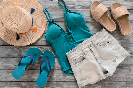 Womens clothing, accessories (denim shorts, straw hat, swimsuit, sandals) on grey wooden background. Trendy fashion outfit. Shopping, travel, summer, beach concept, abstract.  Flat lay