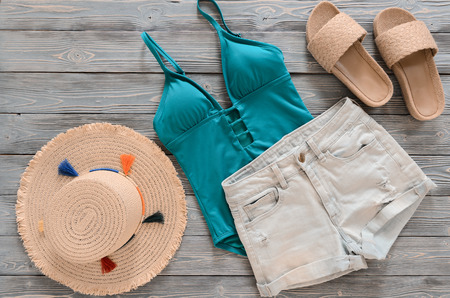 Womens clothing, accessories (denim shorts, straw hat, swimsuit, sandals) on grey wooden background. Trendy fashion outfit. Shopping, travel, summer, beach concept, abstract.  Flat lay Standard-Bild - 98917390