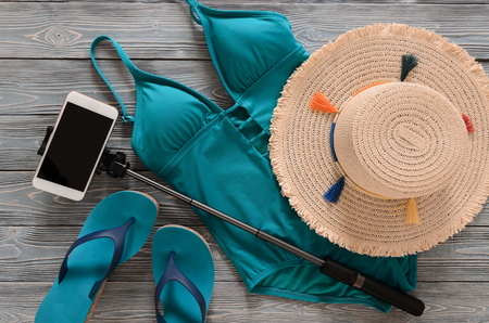 Womens clothing, accessories, shoes (straw hat, blue green swimsuit, flip flops, cellphone, selfie stick) on grey wooden background. Trendy fashion outfit. Shopping, travel, summer, beach, vacation concept, abstract.  Flat lay