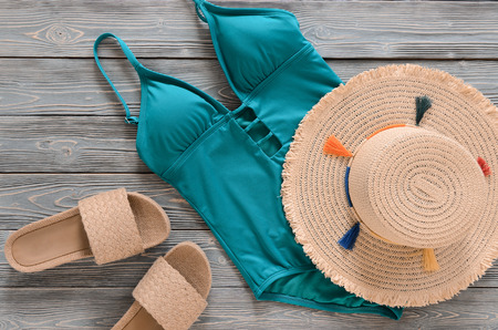 Womens clothing, accessories, shoes (straw hat, blue green swimsuit, sandals) on grey wooden background. Trendy fashion outfit. Shopping, travel, summer, beach concept, abstract.  Flat lay Standard-Bild - 98895332