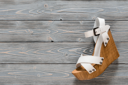 Womens shoes (crisscross wood platform wedges) on grey wooden background. Spring summer collection with copy space. Flat lay. Fashion concept. Template for online store, coupon, offer, promotion, discounts, gift card, deals Standard-Bild