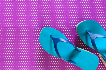 Womens shoes (blue green flip flops) on violet background in polka dots. Shopping, travel, summer, beach concept, abstract.  Flat lay. Copy space