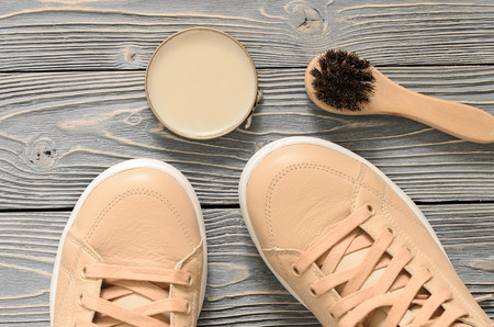 Shoe Care Kit (horsehair buff brush, wax polish neutral cream) on grey wooden background. Leather shoes care and cleaning concept. Top, above view. Flat lay. Copy space Standard-Bild - 99948650