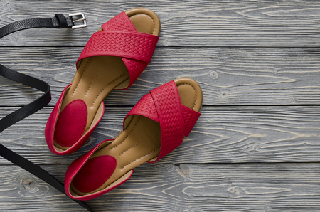 Womens leather shoes and accessories (red flat sandals, yellow handbag, black belt) on grey wooden background. Spring summer collection. Flat lay. Fashion concept Standard-Bild - 101534327