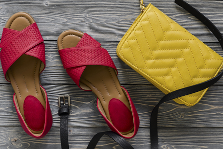 Womens leather shoes and accessories (red flat sandals, yellow handbag, black belt) on grey wooden background. Spring summer collection. Flat lay. Fashion concept