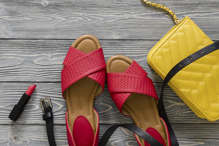 Womens leather shoes and accessories (red flat sandals, yellow handbag, black belt) on grey wooden background. Spring summer collection. Flat lay. Fashion concept. Copy space Standard-Bild