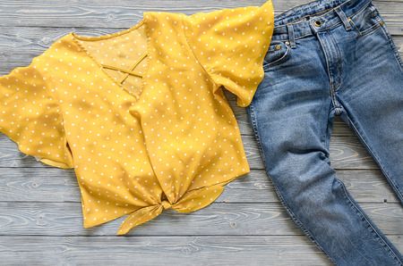 Womens clothing (yellow blouse in polka dot, blue jeans). Fashion outfit. Shopping concept. Flat lay. Trendy, saturated colors. Spring summer collection