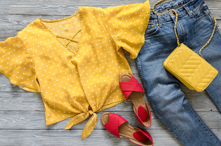 Womens clothing, accessories, shoes (yellow blouse in polka dot, blue jeans, leather red sandals,  yellow crossbody bag). Fashion outfit. Shopping concept. Flat lay. Trendy, saturated colors. Spring summer collection