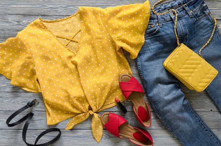 Womens clothing, accessories, shoes (yellow blouse in polka dot, blue jeans, leather red sandals,  yellow crossbody bag, lipstick). Fashion outfit. Shopping concept. Flat lay. Trendy, saturated colors. Spring summer collection Standard-Bild
