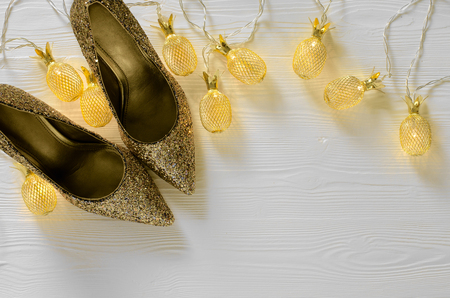 Womens gold chunky glitter pumps. Shoes for wedding, christmas, new year, evening, cocktail, night out. Golden stiletto heels. Flat lay. Footwear on white wooden background with copy space Standard-Bild - 107698359