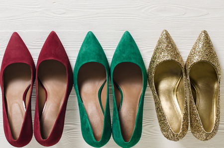 Fashion womens shoes (pumps). Classic christmas colors (red, green, gold). Footwear on white wooden background with copy space. Template for online store, website, banners. Flat lay, top down view Standard-Bild - 107698364