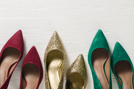 Fashion womens shoes (pumps). Classic christmas colors (red, green, gold). Footwear on white wooden background with copy space. Template for online store, website, banners. Flat lay, top down view Standard-Bild - 107698365