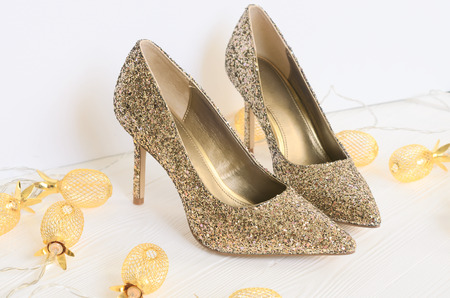 Womens gold chunky glitter pumps. Shoes for wedding, christmas, new year, evening, cocktail, night out. Golden stiletto heels. Flat lay. Footwear on white wooden background with copy space Standard-Bild