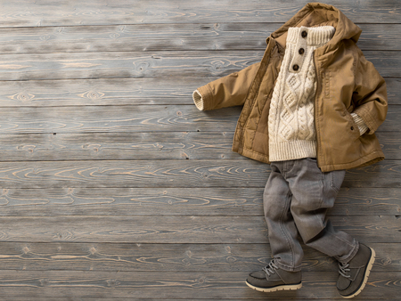 Childrens clothing, shoes (knit sweater, hooded canvas jacket, skinny gray jeans, suede boots). Outfit for little boy. Winter, autumn collection. Fashion, shopping concept. Template for online store, selling. Top view, flat lay Standard-Bild