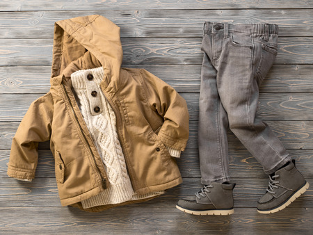 Childrens clothing, shoes (knit sweater, hooded canvas jacket, skinny gray jeans, suede boots). Outfit for little boy. Winter, autumn collection. Fashion, shopping concept. Template for online store, selling. Top view, flat lay Standard-Bild - 108857510