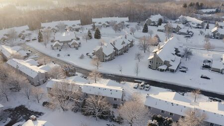 Aerial view of residential houses, condo, townhouses covered snow at winter season. Establishing shot of american neighborhood, suburb at wintertime.  Real estate, Midwest, sunny morning Standard-Bild