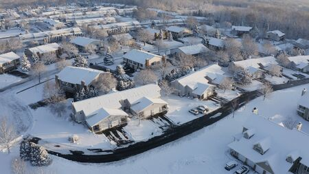 Aerial view of residential houses covered snow at winter season. Establishing shot of american neighborhood, suburb.  Real estate, drone shots, sunny morning, sunlight, from above.
