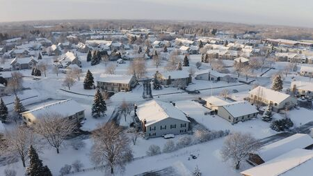 Aerial view of residential houses, condo, townhouses covered snow at winter season. Establishing shot of american neighborhood, suburb at wintertime. Real estate, Midwest, sunny morning
