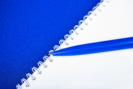 Spiral notebook with pen on blue background photo