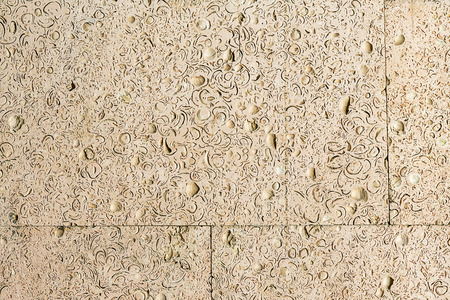 coquina: abstract background of coquina. Stone facing of a wall. Stone texture of warm colors.