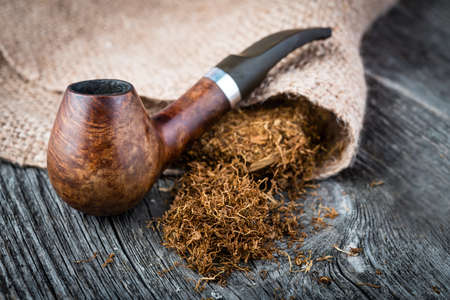 smoking pipe with  tobacco leaves on wooden background Stock Photo