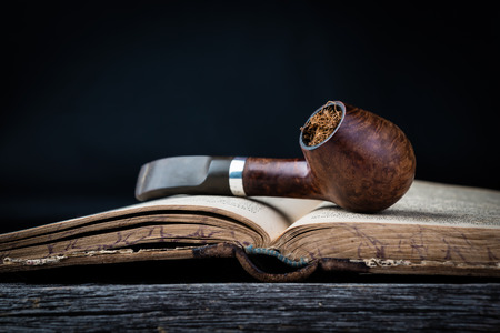 Closeup of smoking pipe on the opened old book in wooden grey table.