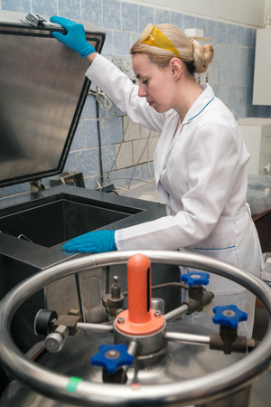 programm: Scientist working in a liquid nitrogen bank. Cryopreservation of reproductive cells in programm mode.