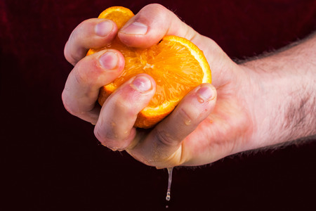 irritation: Male hand squeezing orange on mulberry background. Concept of anger and irritation