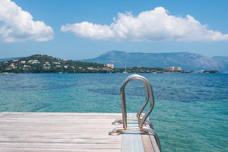 pontoon: Wooden pontoon stretching into the sea in Greece, Corfu Stock Photo
