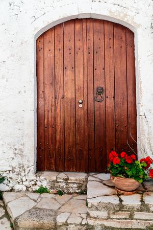 greek pot: Porta di legno e rosso geranio in vaso, Casa greca tradizionale all'isola di Corfù