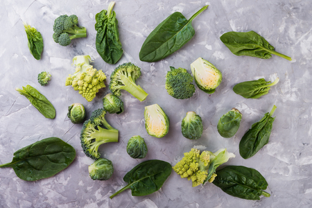 Collection of fresh green vegetables on grey concrete background, broccoli,  brussels sprouts, kiwi, avocado