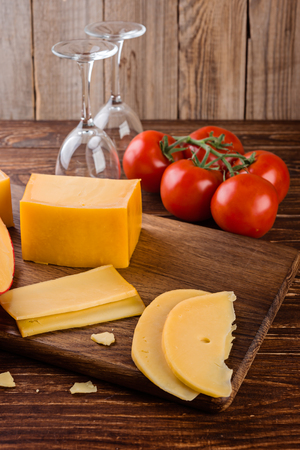 Cheese assortment and tomates on a on wooden background, selective focus