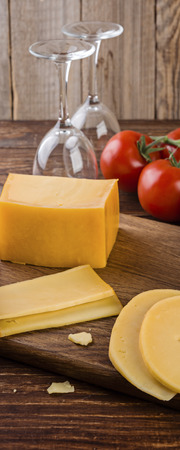 Cheese assortment and tomates on a on wooden background