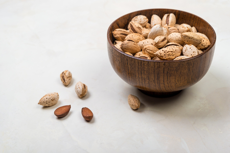 raw almonds in a wooden bowl 写真素材
