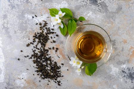 Jasmine tea with jasmine flowers on a glass cup, top view