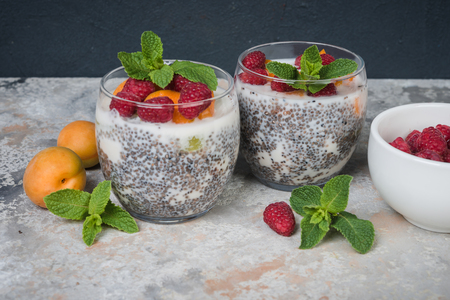 Chia seed pudding  with raspberries and apricots on grey concrete table