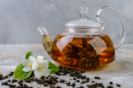 Green tea with jasmine flowers in a glass pot  on grey  background
