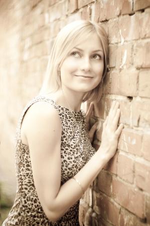 Cute  blonde lady standing near a brick wall photo