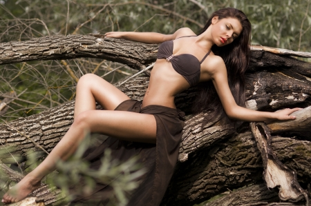 nude outdoors: A young girl in a beautiful bathing suit lying on a fallen tree, portrait series of girls in nature