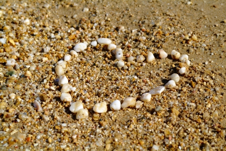 sand writing: shape of the heart, lined with pebbles on the shore of the Sea Stock Photo